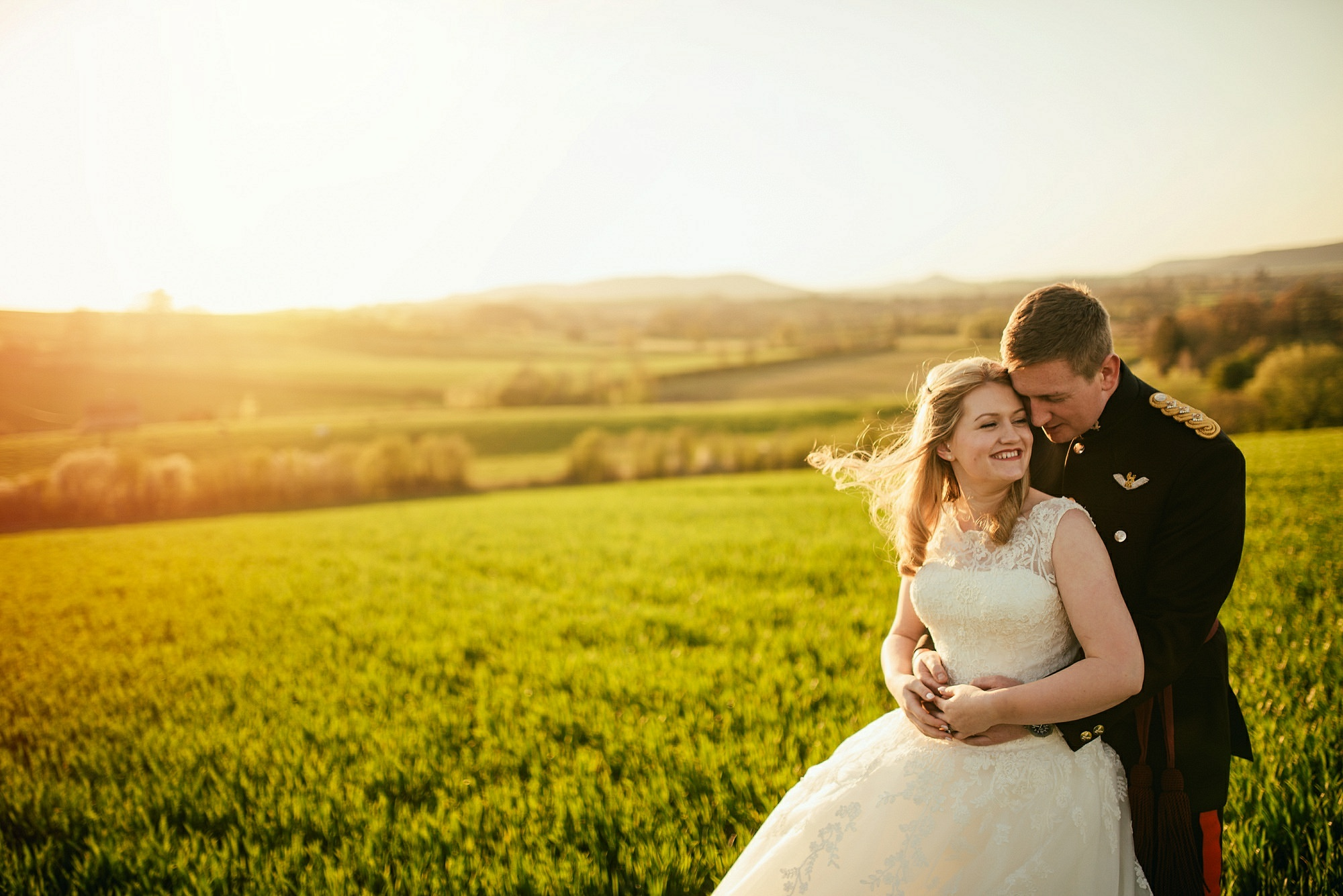 bride and groom in field golden hour