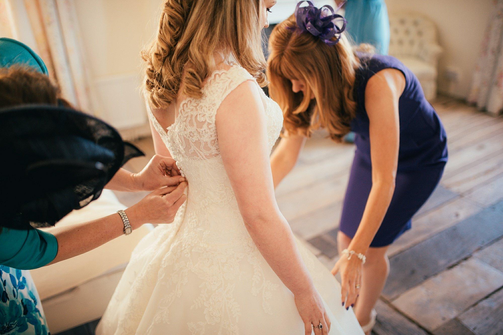 bride having dress done up