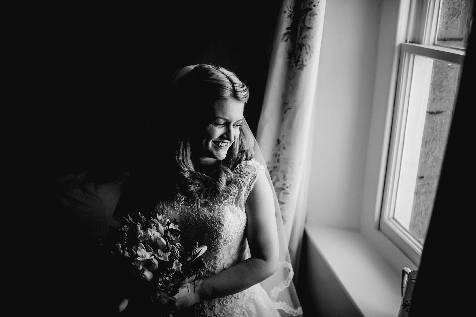 bride looking out of window in black and white