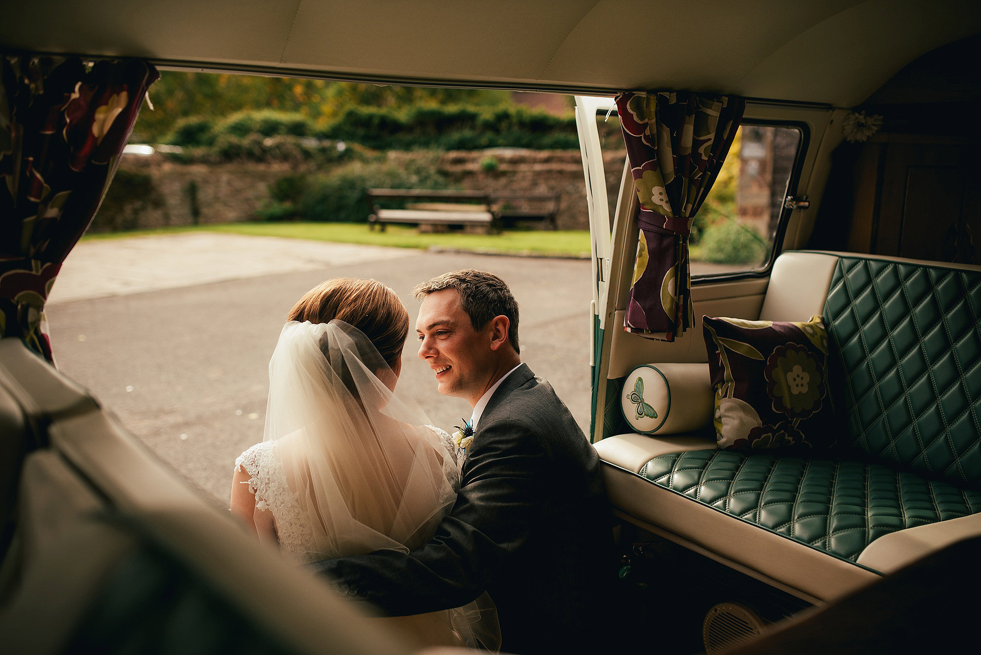 Bride and groom sat in VW Camper Van outside Flanesford Priory Herefordshire