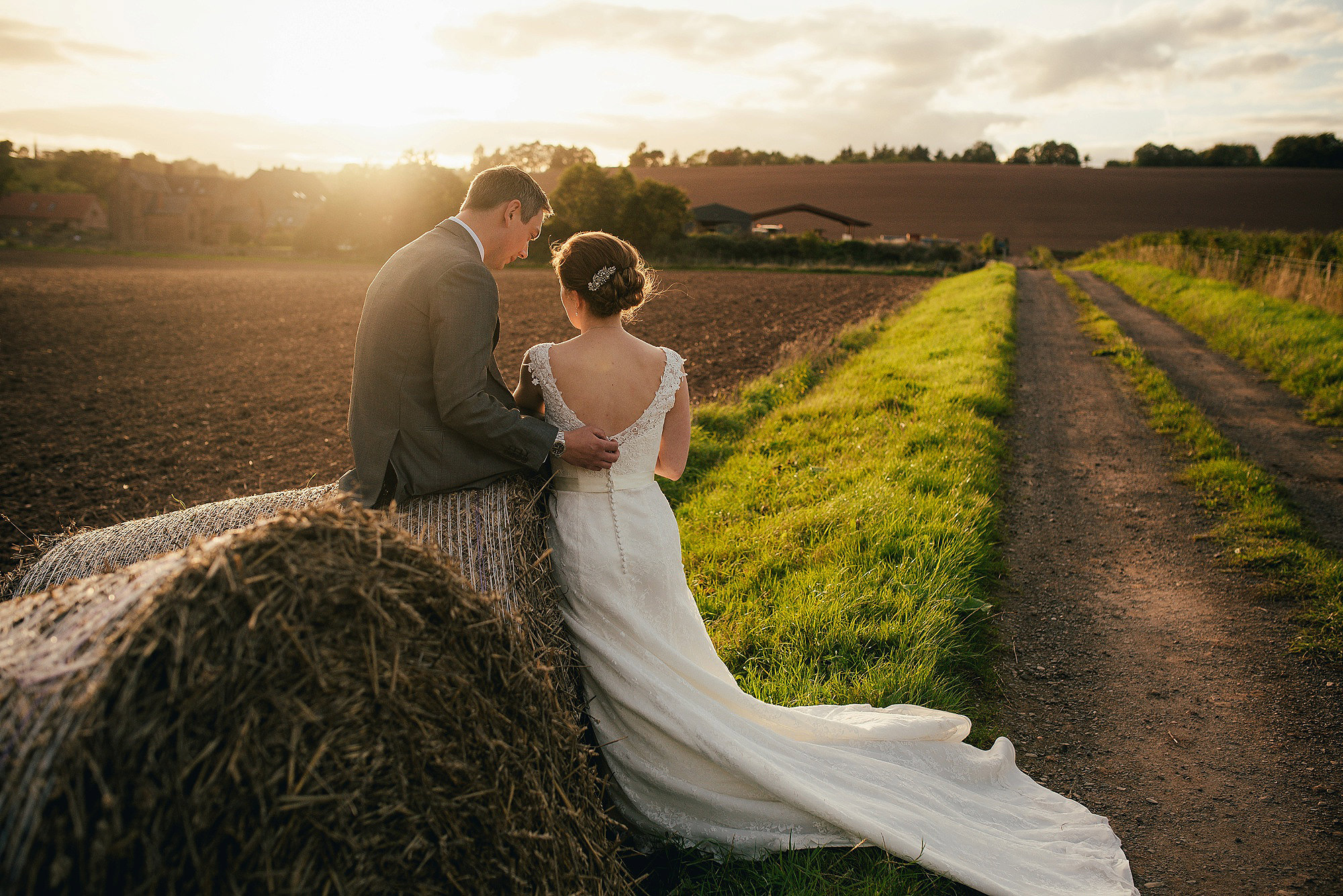couple in sunshine on hay bale