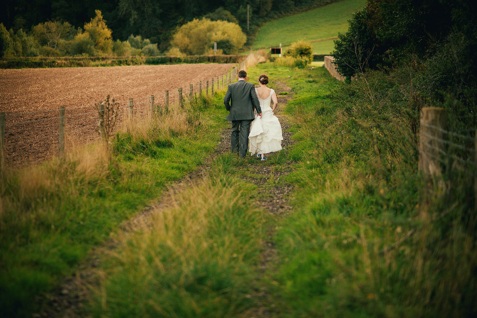 bride and groom in field during golden hour