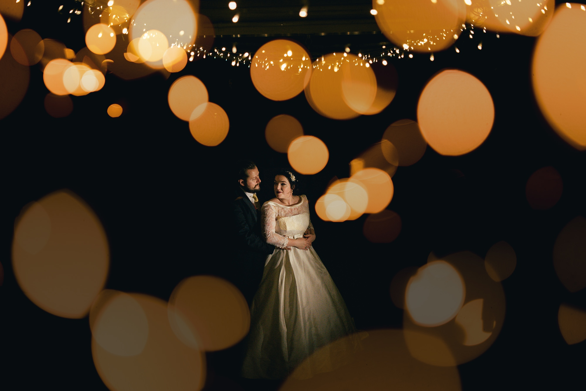 bride and groom portrait bokeh fairy lights