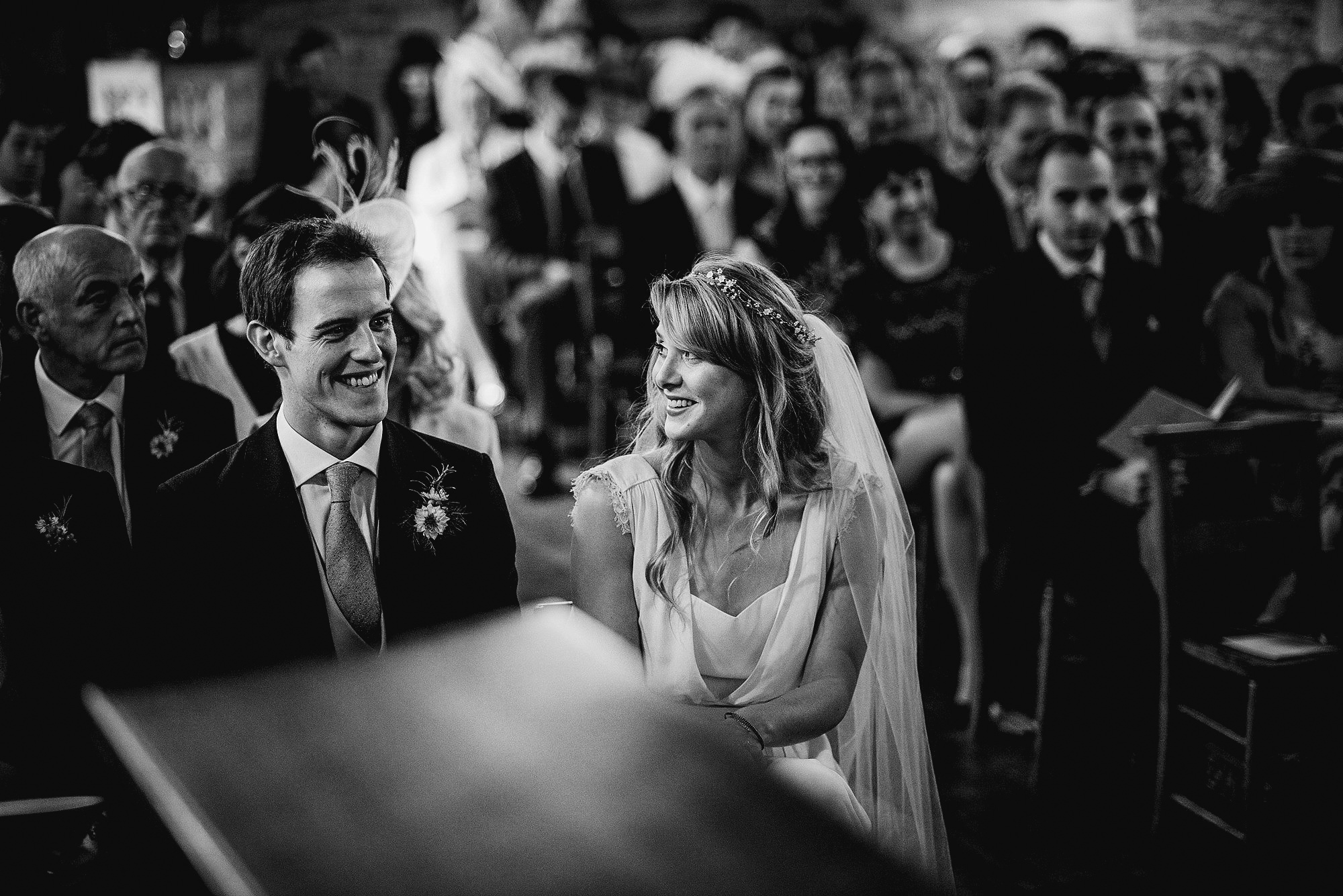 bride and groom during church ceremony in black and white