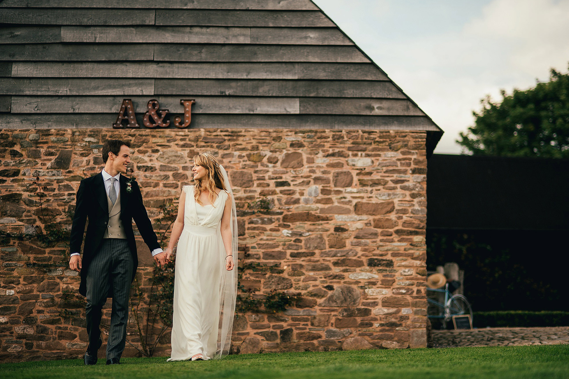 bride and groom walking by rustic barn