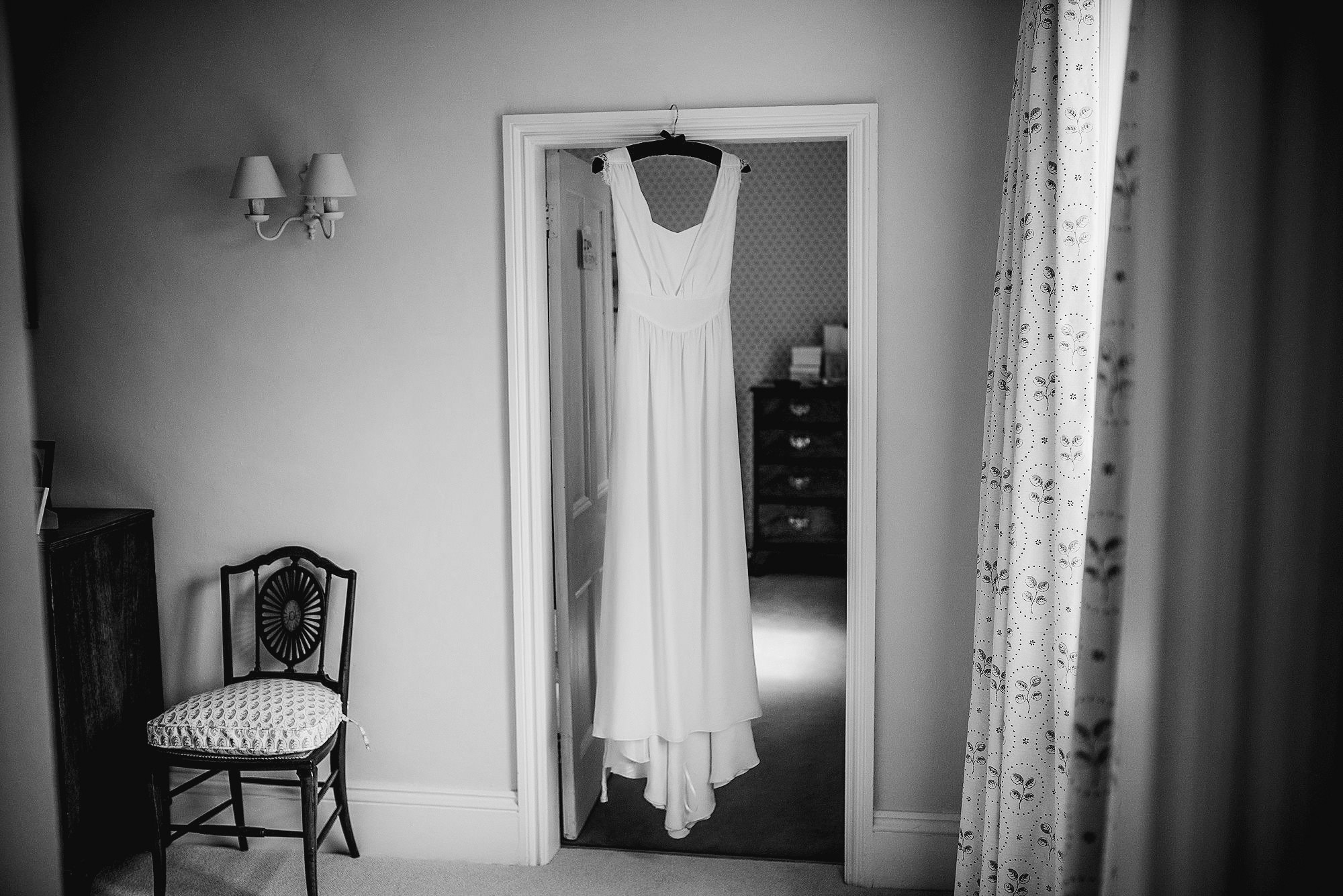 wedding dress hanging in door way